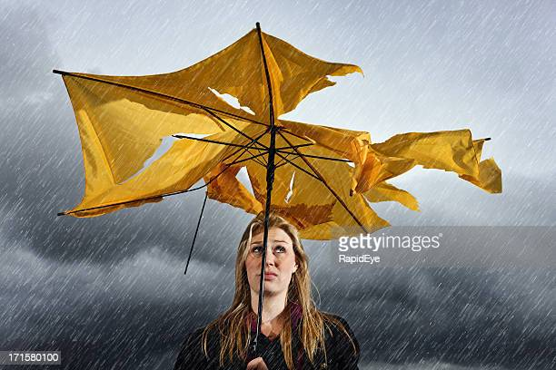 Beautiful unhappy blonde with ruined umbrella getting soaked in thunderstorm