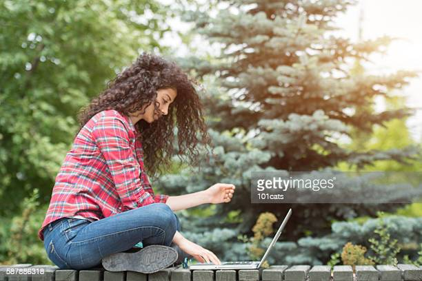 Beautiful university student study with laptop in the campus garden