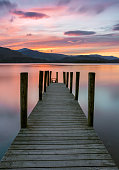A beautiful vibrant pink and purple sunset with Ashness Jetty in the foreground at Derwentwater in the Lake District, UK.