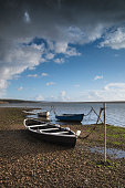 Beautiful sunset landscape image of boats moored in Fleet Lagoon in Dorset England