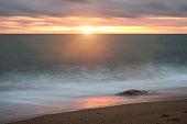 Beautiful sunset landscape image of Burton Bradstock golden cliffs in Dorest England