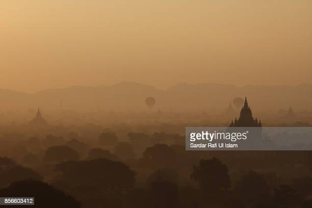 Beautiful view of hot air balloons flying over the pagodas in the misty plains of Bagan, Mandalay Region, Myanmar.
