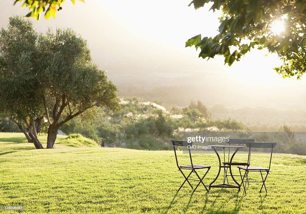 Beautiful view of lawn with empty table and chairs : Stock Photo