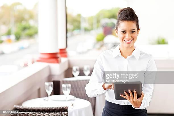 美しいウェイトレス、デジタルタブレットのレストランで