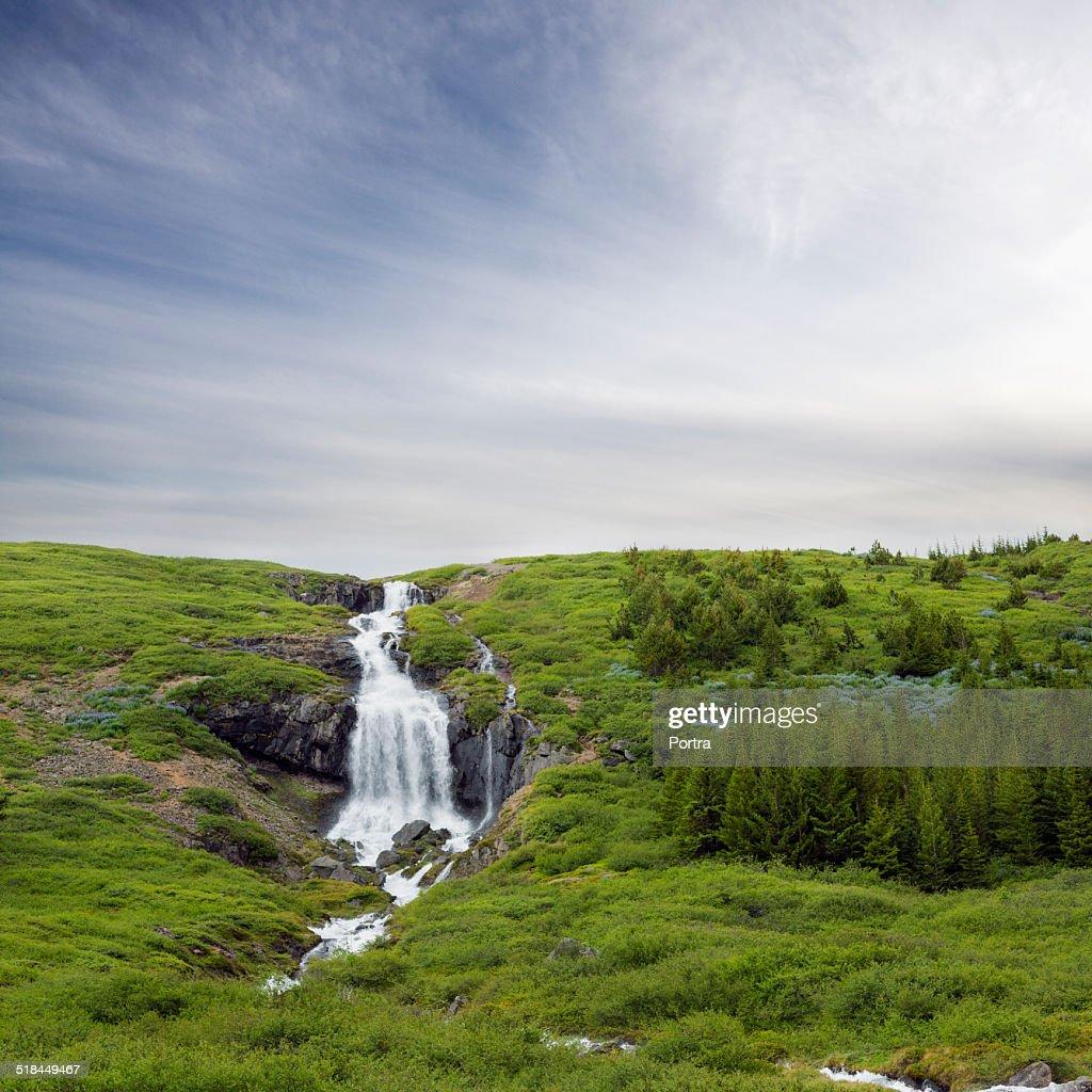 Beautiful waterfall on mountain against sky