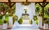 Beautiful wedding arch for the ceremony in the garden in sunny weather.