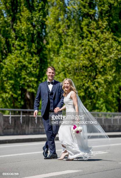 beautiful wedding couple in their festive clothes walking happy with a big smile on a street, he wears his wedding suit with fly and she her white wedding dress with vein, she holds her bridal flowers consisting of white and pink peonies in her left hand