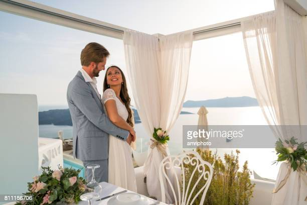 beautiful wedding couple standing together at dinner table outside luxury restaurant in greece