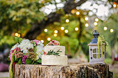 Beautiful wedding decoration with cake, bouquet of flowers and a lantern on background of nature