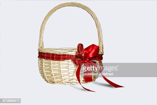 Beautiful wicker basket with red bow isolated on white background : Stock Photo