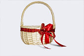 Woven container with round handle b of soft golden color, decorated with a bow of red ribbon