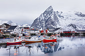 Beautiful winter landscape of picturesque harbor with fishing boat and traditional Norwegian rorbus in Lofoten islands, Norway