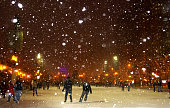 People enjoying ice skating during snowy night in Chicago