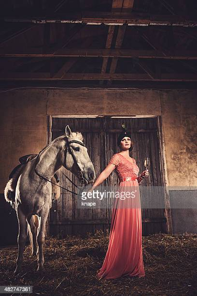 Beautiful woman and horse in riding house