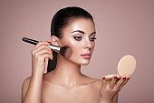 Beautiful Woman applies Skin Tone with Brush. Beautiful Woman face. Perfect Makeup. Skincare Foundation. Brushes Makeup Artist