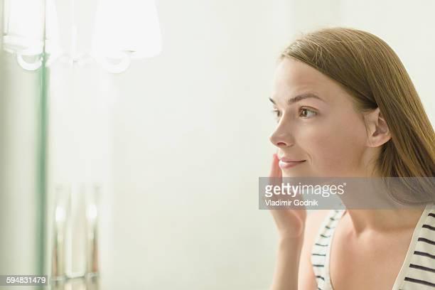 Beautiful woman applying cream on face in domestic bathroom