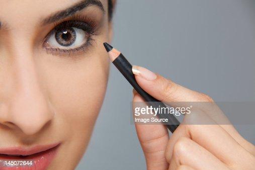 Beautiful woman applying eyeliner : ストックフォト