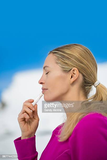 Beautiful woman applying lip balm on her lips, Crans-Montana, Swiss Alps, Switzerland