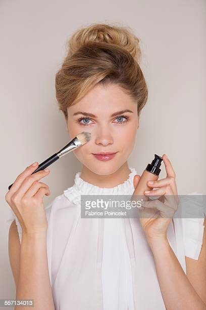 Beautiful woman applying make-up with blusher