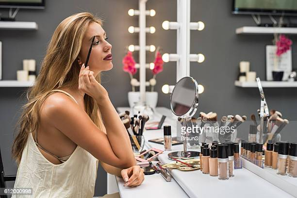 Beautiful woman applying mascara on her eyelashes in beauty salon.
