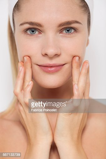 Beautiful woman applying moisturizer on her face