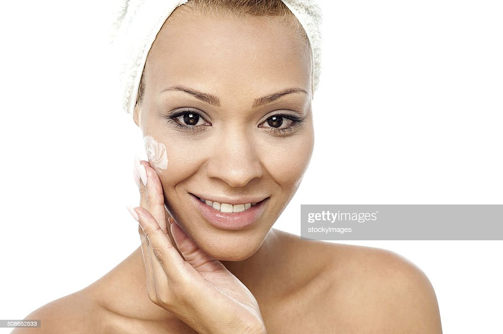 Beautiful woman applying moisturizer : Stock Photo