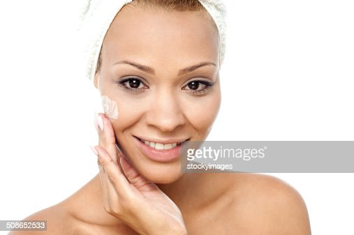 Beautiful woman applying moisturizer : Stock Photo
