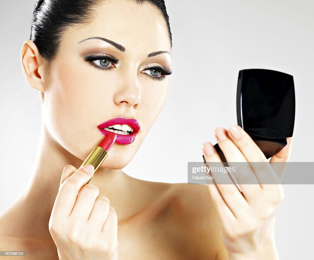 Beautiful woman applying pink lipstick on lips : Stock Photo