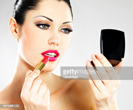 Beautiful woman applying pink lipstick on lips : Stock Photo