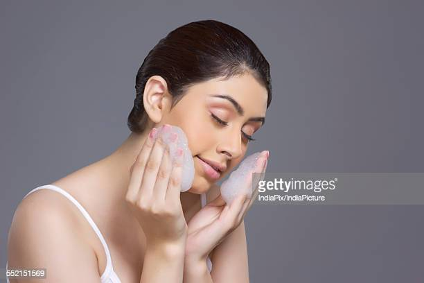 Beautiful woman applying soap sud on face against gray background
