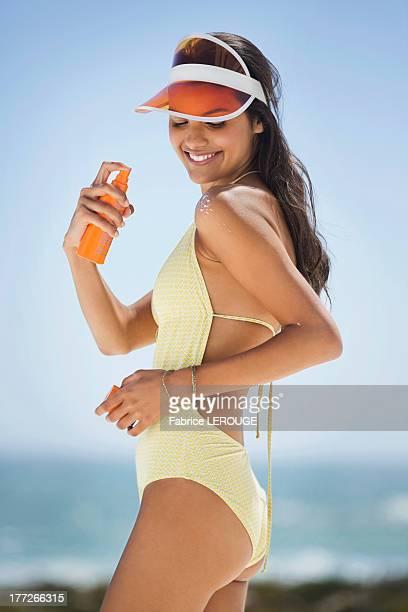 Beautiful woman applying suntan lotion on her shoulder