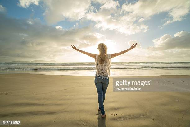Beautiful woman arms outstretched on beach at sunrise