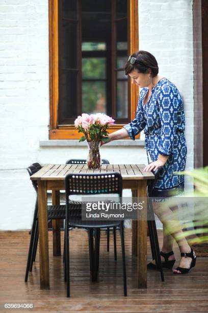 A beautiful woman arranging a bouquet of roses in a vase on an outdoor table