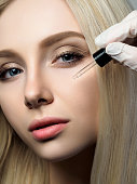 Portrait of beautiful blonde woman at beauty shop. Cosmetologist applying beauty drops. Luxury skincare, beautician and skin care concept.