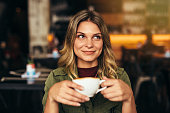 Portrait of beautiful young woman sitting at cafe with cup of coffee and looking away. Caucasian female having coffee at cafe