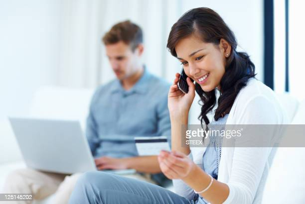 Beautiful woman at home paying bills with credit card