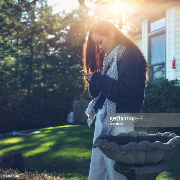 beautiful woman at yard of house,texting messages