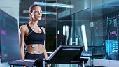 Beautiful Woman Athlete Wearing Sports Bra with Electrodes Connected to Her, Walks on a Treadmill in a Sports Science Laboratory. In the Background Laboratory. Medium Shot.