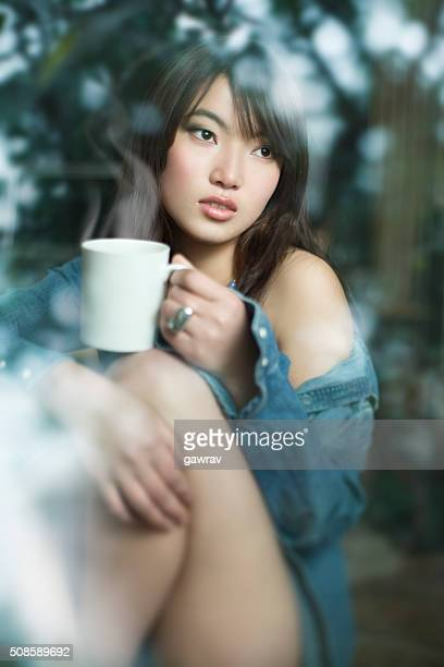 Beautiful woman behind glass window at home with coffee mug.