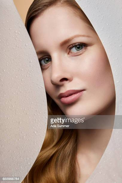 beautiful woman between frosted glas with water droplets on it