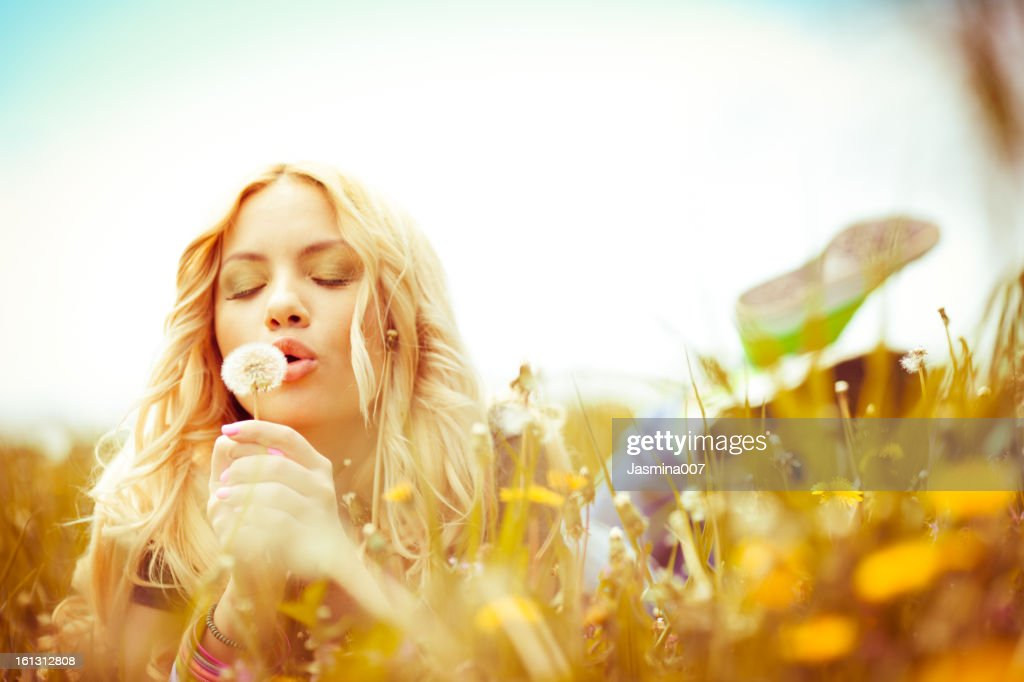 Beautiful woman blowing dandelions outdoors : Stock Photo