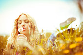 Beautiful woman blowing dandelions outdoors