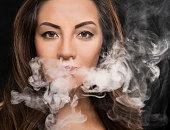 Beautiful woman blowing vape smoke