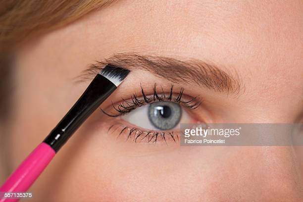 Beautiful woman brushing eyebrow
