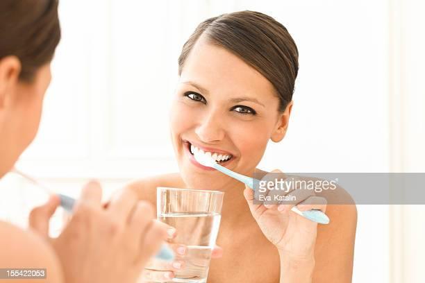 Bela mulher escovar os dentes
