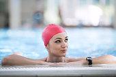 Beautiful woman cap smiling looking to camera at border of swimming pool.