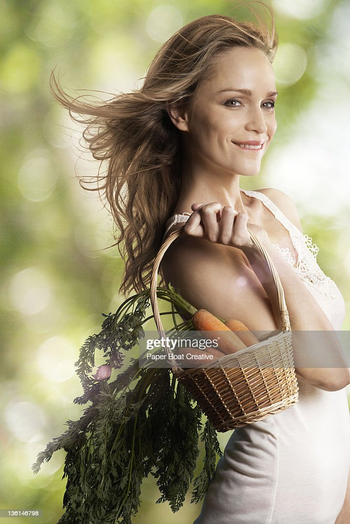 beautiful woman carrying a basket full of carrots : Stock Photo