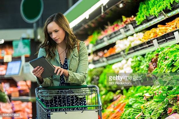 Beautiful woman checks tablet while shopping