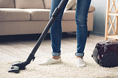 Cropped image of woman in jeans using a vacuum cleaner while cleaning her house