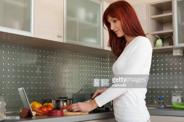 Beautiful woman cooking and looking for a recipe online